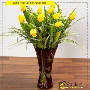 bright yellow tulips in maroon vase